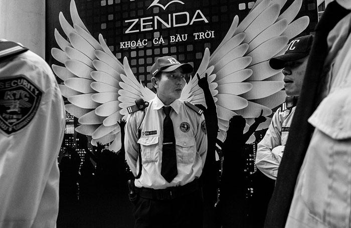 Охранник перед рекламным щитом с расправленными крыльями.